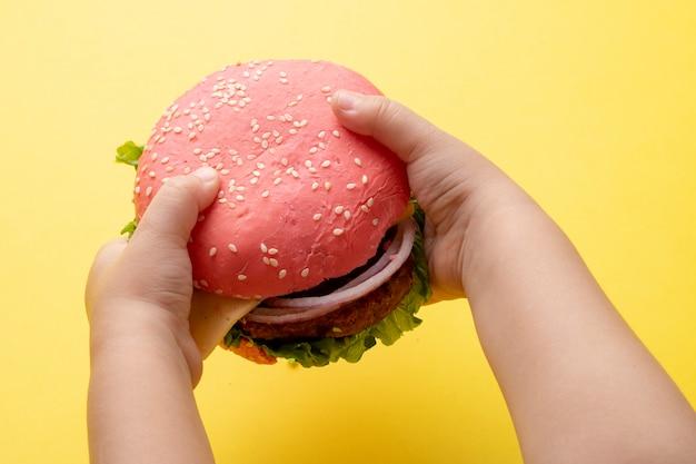 Hambúrguer rosa nas mãos do garoto