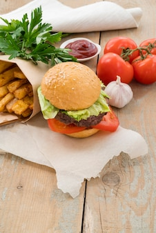 Hambúrguer saboroso batatas fritas e tomates