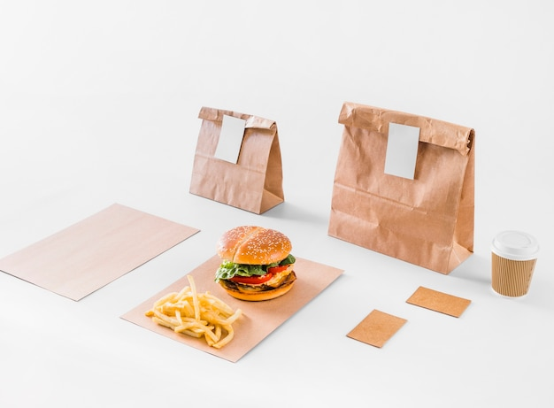 Hambúrguer saboroso; batatas fritas; pacotes e copo de eliminação na superfície branca