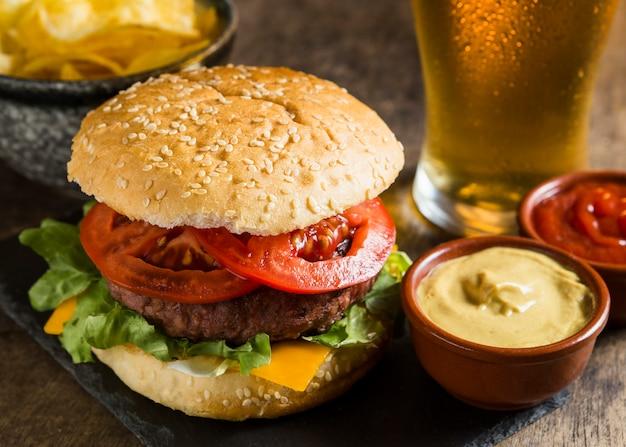 Hambúrguer saboroso com copo de cerveja e mostarda