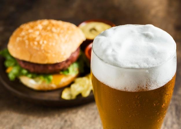 Hambúrguer saboroso com copo de cerveja espumosa