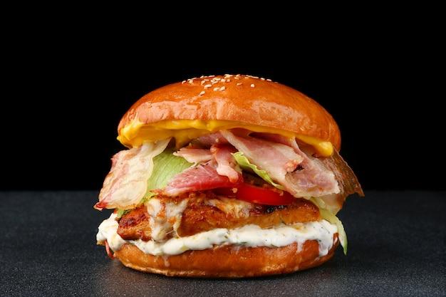 Hambúrguer saboroso com frango e bacon no fundo isolado escuro. hambúrguer caseiro com molho e legumes frescos