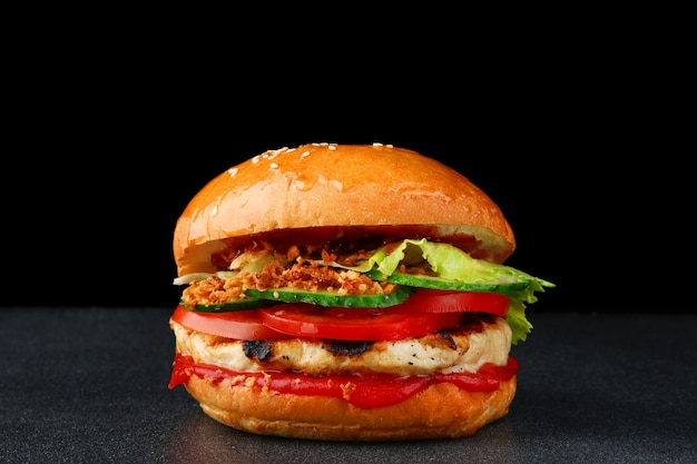 Hambúrguer saboroso com frango no fundo escuro isolado. hambúrguer caseiro com molho e legumes frescos