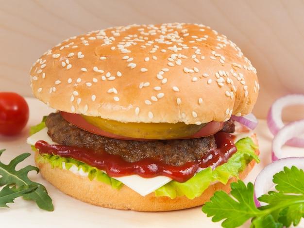Hambúrguer saboroso com patty de carne em uma placa de madeira