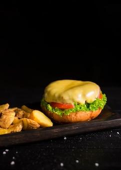 Hambúrguer saboroso com queijo derretido e batatas fritas