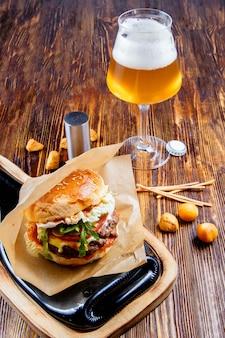 Hambúrguer saboroso com um copo de cerveja na mesa de madeira