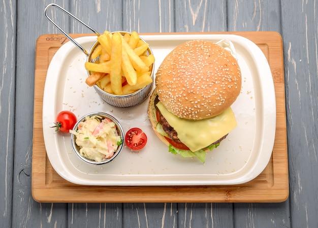 Hambúrguer saboroso e apetitoso cheeseburger. em uma mesa de madeira