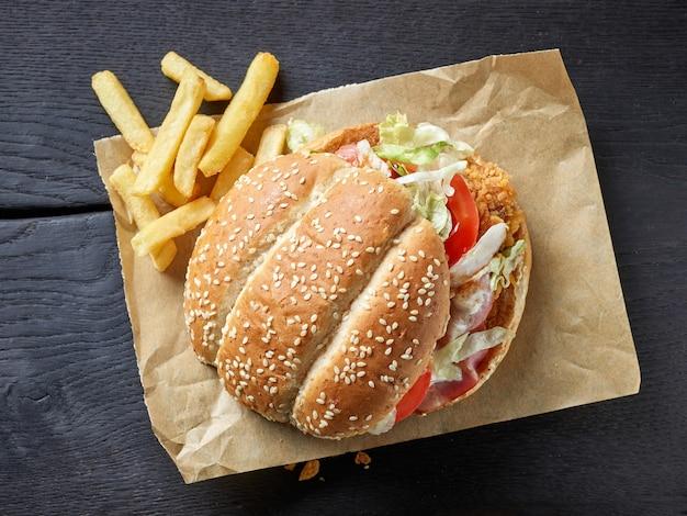 Hambúrguer saboroso e fresco e batatas fritas na mesa de madeira preta, vista superior