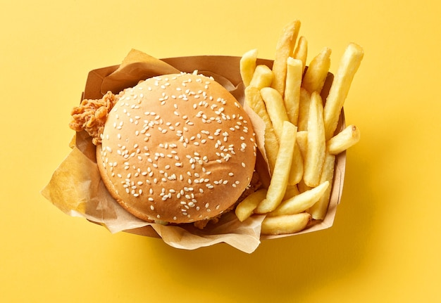 Hambúrguer saboroso e fresco e batatas fritas no fundo de papel amarelo, vista superior