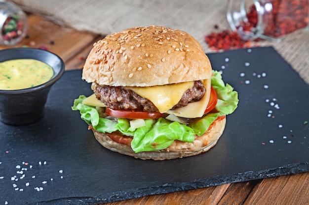 Hambúrguer saboroso fresco com queijo, alface, tomate, pepino em pedra preta com molho. fast-food americano. cheeseburger com espaço de cópia no fundo de madeira. feche acima, foco seletivo. comida. menu de grelhados