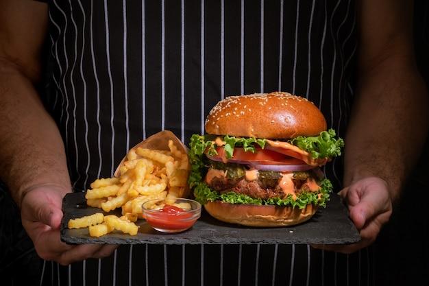 Hambúrguer saboroso fresco e batatas fritas seguram nas mãos.
