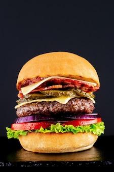 Hambúrguer saboroso fresco em um fundo preto.