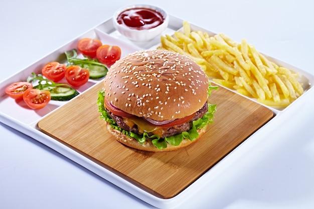 Hambúrguer saboroso suculento sobre uma tábua de madeira com batatas fritas, legumes e ketchup. composição isolada em um fundo branco e em uma bandeja branca do serviço.