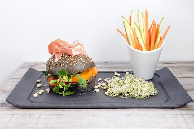 Hambúrguer saudável com hamon, tomate, micro verduras e pães integrais pretos, palitos de legumes na placa de ardósia preta sobre a mesa de madeira. limpe comer, fazer dieta, conceito de comida de desintoxicação.