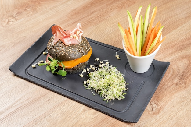 Hambúrguer saudável com hamon, tomate, micrverduras e pães integrais pretos, palitos de vegetais no quadro de ardósia preta