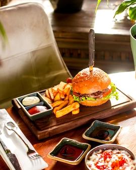 Hambúrguer servido com batata frita, ketchup e maionese