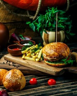 Hambúrguer servido com ervas e batatas fritas