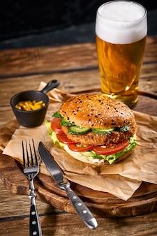 Hambúrguer suculento, batatas fritas, molhos e um copo de cerveja gelada em um fundo escuro de madeira