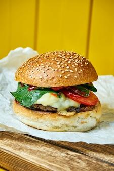 Hambúrguer suculento com queijo derretido com um rissol de carne em papel ofício. mesa amarela. rua, fast food. fechar-se..