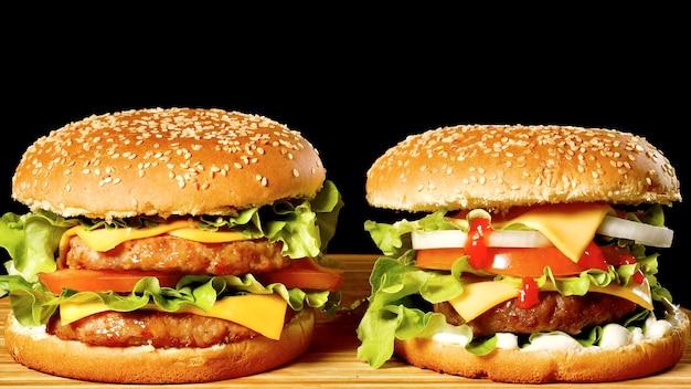 Hambúrguer suculento em uma mesa de madeira, cheeseburguer com alface e tomate em um pão
