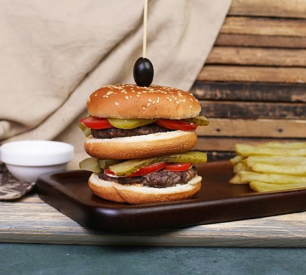 Hambúrguer triplo com carne e legumes.