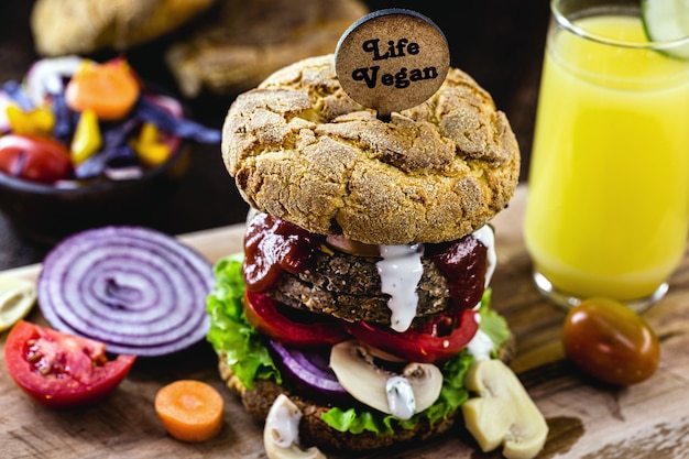 Hambúrguer vegano, com hambúrguer à base de soja. placa de madeira escrita em inglês: vegan life