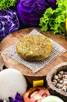 Hambúrguer vegano sem carne feito com sementes, vegetais, soja, grão de bico, milho e lichia, rodeado de vegetais.