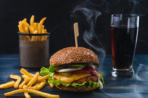 Hamburguer vegetariano com batatas fritas e bebida na mesa de madeira