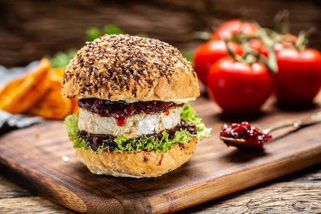 Hambúrguer vegetariano com molho de camembert e cranberry em uma placa de madeira rústica.