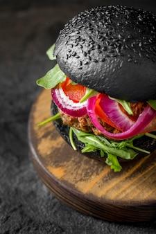 Hambúrguer vegetariano de ângulo alto com pãezinhos pretos na tábua de cortar