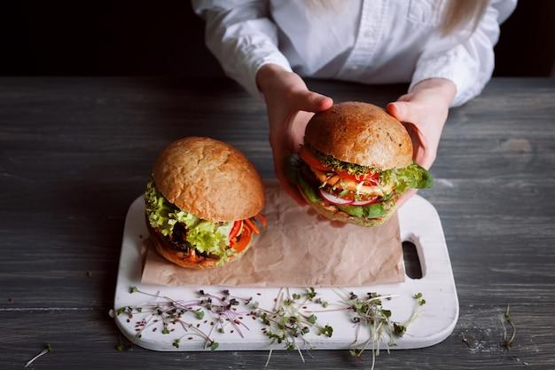 Hambúrguer vegetariano de dar água na boca e delicioso em uma superfície de madeira preta.