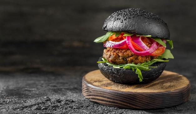 Hambúrguer vegetariano de vista frontal com pãezinhos pretos na tábua