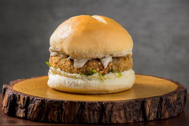 Hambúrguer vegetariano saboroso caseiro feito de repolho. em uma fatia rústica de árvore com fundo cinza.
