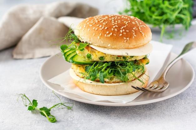 Hambúrguer vegetariano saudável com brotos de ovo e ervilha e microgreen de sementes, salada fresca, fatia de pepino em uma placa de madeira de corte sobre fundo claro. foco seletivo