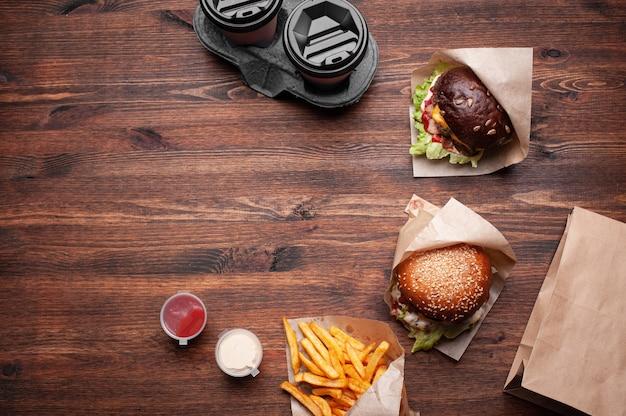 Hambúrgueres, batatas fritas com molhos e café para levar vista de cima na madeira. tiro horizontal.
