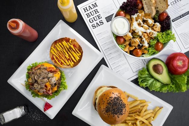 Hambúrgueres, batatas fritas, salada e menu de restaurante
