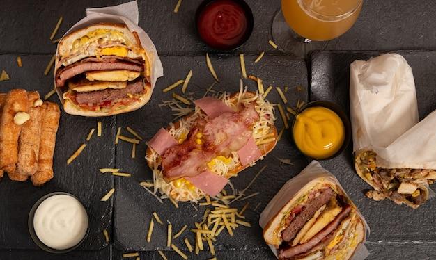 Hambúrgueres, burritos pãezinhos fritos e vários molhos na superfície preta