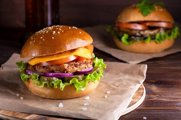 Hambúrgueres caseiros com carne e pepinos na madeira