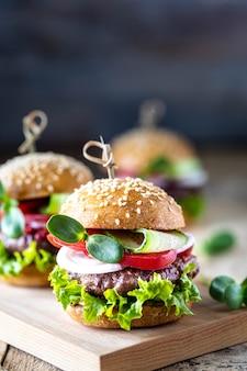 Hambúrgueres caseiros com costeleta, alface fresca, tomate, cebola em uma mesa de madeira. copie o espaço