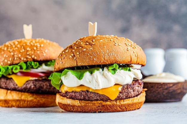 Hambúrgueres caseiros de carne com queijo, maionese, picles e vegetais, fundo cinza.