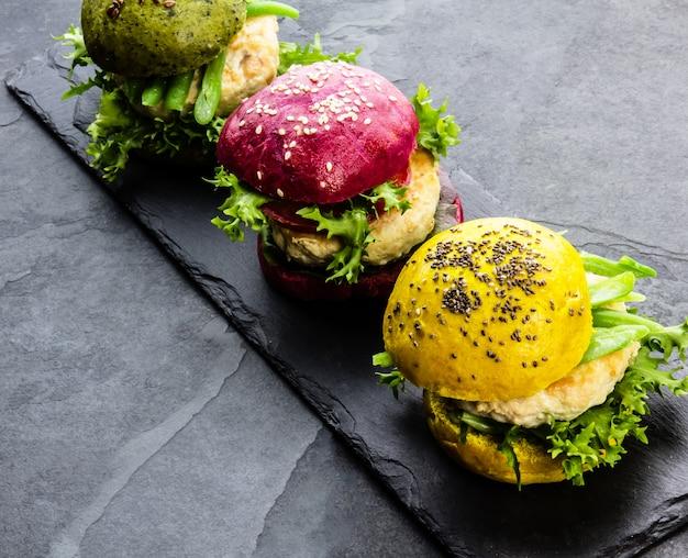 Hambúrgueres coloridos na placa de ardósia