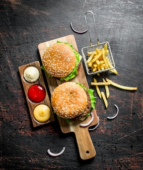 Hambúrgueres com batata frita e vários molhos. em fundo escuro rústico