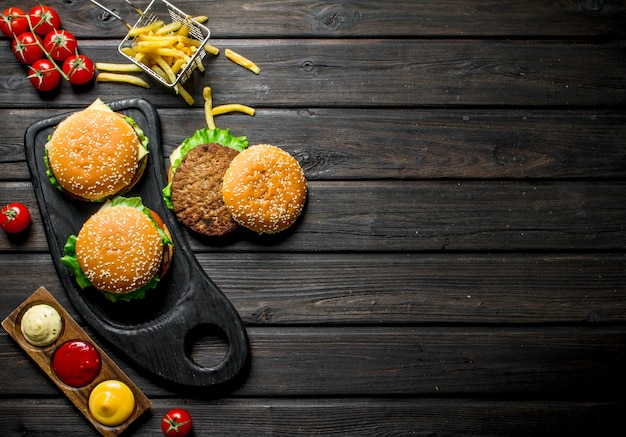 Hambúrgueres com batata frita, molhos e cereja. em fundo preto de madeira
