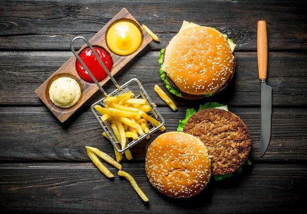Hambúrgueres com batata frita, molhos e uma faca. em fundo de madeira