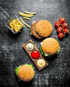 Hambúrgueres com batata frita, tomate e molhos diversos. sobre fundo preto rústico