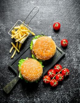 Hambúrgueres com batatas fritas e tomates na mesa rústica preta.