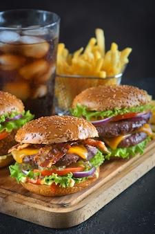 Hambúrgueres com batatas fritas e um copo de cola