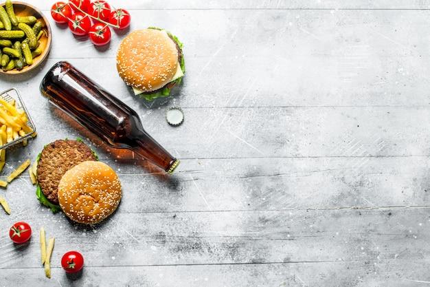 Hambúrgueres com cerveja em garrafa, pepinos e batatas fritas. na mesa de madeira branca