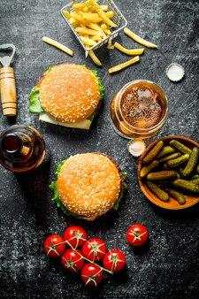 Hambúrgueres com cerveja em um copo e uma garrafa. sobre fundo preto rústico