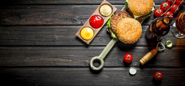 Hambúrgueres com cerveja em uma garrafa e um copo. na mesa de madeira preta